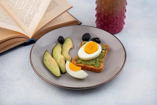 Vista lateral de fatias de abacate frescas com abacate em uma fatia de pão com ovo escalfado em um prato com coquetel em uma jarra de vidro e livro na superfície branca