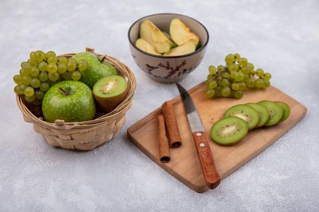 Vista lateral de fatias de kiwi com uvas, canela e uma faca em uma placa de corte com maçãs verdes em uma cesta e as fatias em uma tigela sobre um fundo branco