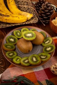 Vista lateral de fatias de kiwis em um prato e cacho de bananas em uma cesta de vime na madeira