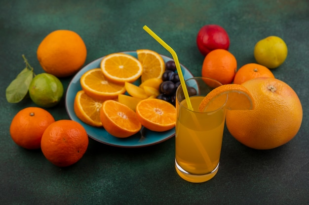 Vista lateral de fatias de laranja com ameixa cereja em um prato azul com suco de laranja, toranja e limão com limão em um fundo verde