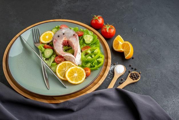 Vista lateral de fatias de limão e talheres de peixe cru e legumes frescos em um prato cinza com especiarias em uma toalha de cor escura na superfície preta