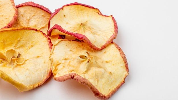 Vista lateral de fatias de maçã seca no fundo branco