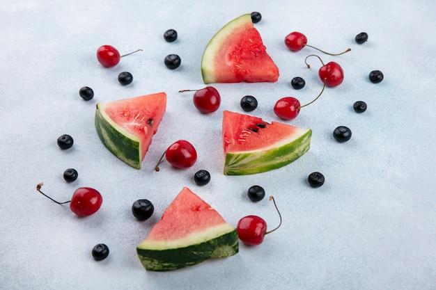Vista lateral de fatias de melancia com cerejas e mirtilos