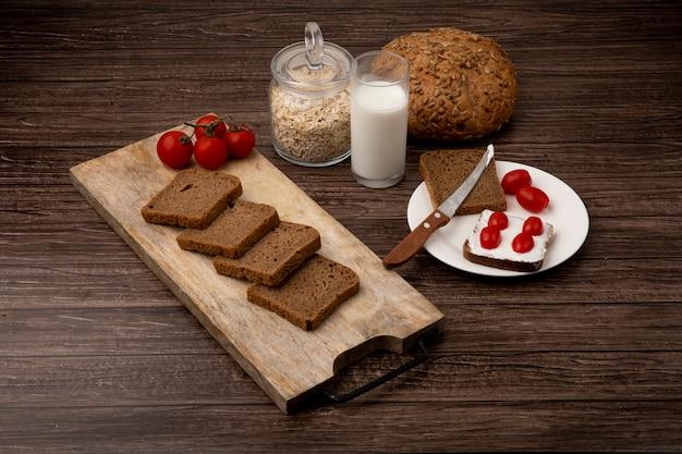 Vista lateral de fatias de pão de centeio e tomates na tábua com espiga de leite e flocos de aveia em fundo de madeira