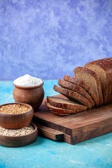 Vista lateral de fatias de pão preto picado ao meio em tábuas de madeira farinha de aveia de trigo em tigelas sobre fundo azul claro