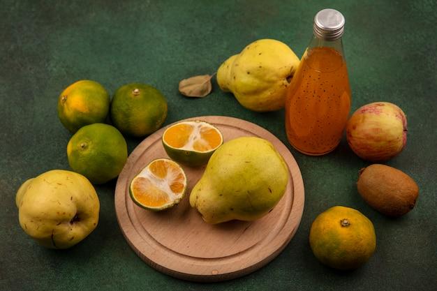 Vista lateral de fatias de tangerina em um suporte com peras, maçã, kiwi e uma garrafa de suco em uma parede verde