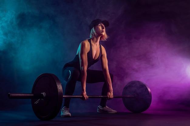 Vista lateral de fisiculturista feminina fazendo levantamento terra com barra