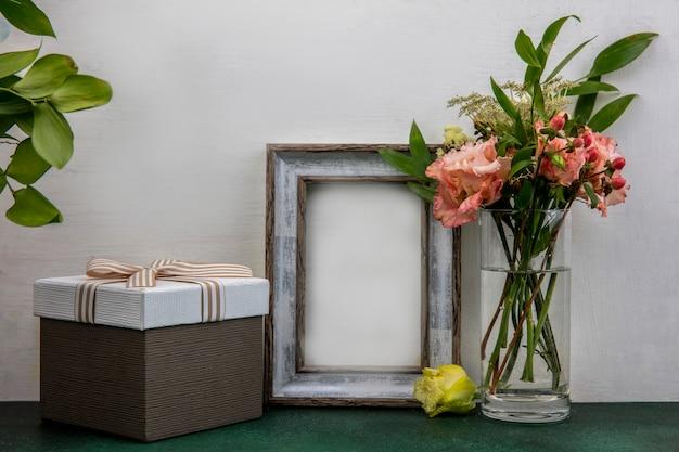 Vista lateral de flores bonitas e frescas com folhas em um copo na superfície branca com espaço de cópia
