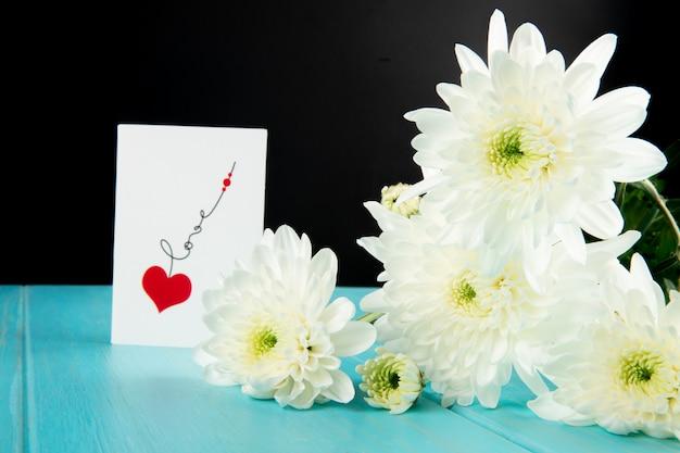 Vista lateral de flores de crisântemo de cor branca e um cartão postal sobre fundo azul de madeira