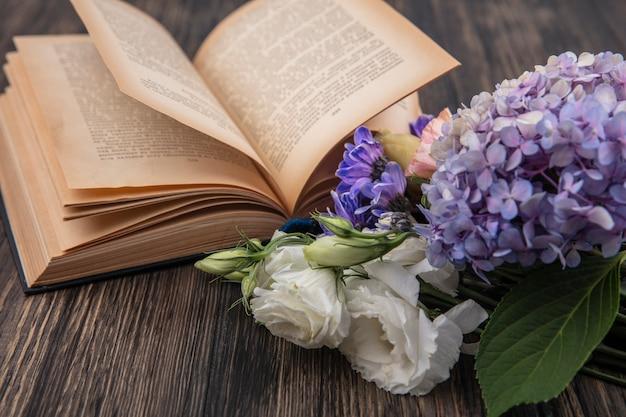 Vista lateral de flores e livro aberto em fundo de madeira