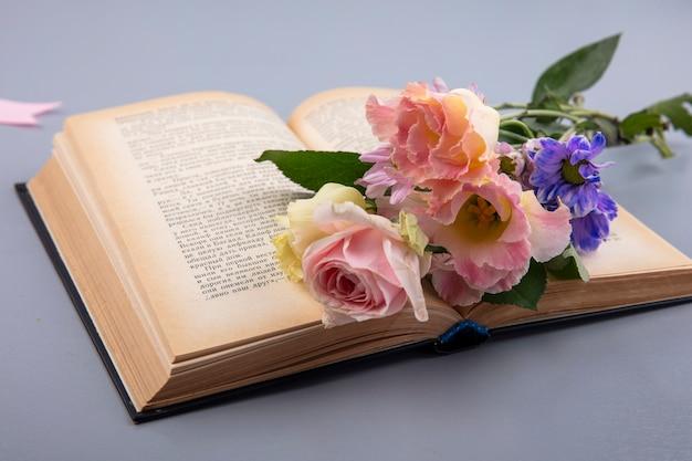Vista lateral de flores em livro aberto em fundo cinza