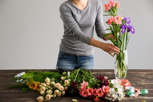 Vista lateral de flores, florista colocar buquê em um vaso