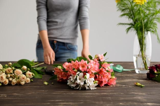 Vista lateral de flores, florista em processo de fazer buquê
