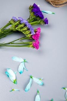 Vista lateral de flores rosa e roxo statice com pétalas de flores espalhadas na mesa branca