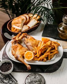 Vista lateral de frango assado com batatas fritas em chapa branca sobre uma tábua de madeira