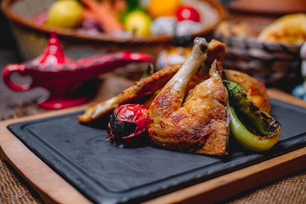 Vista lateral de frango assado com legumes grelhados em uma placa preta