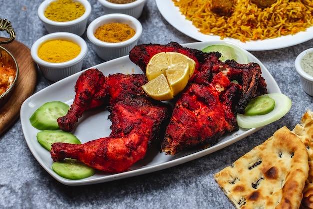 Vista lateral de frango assado com tempero de limão e pepino em cima da mesa