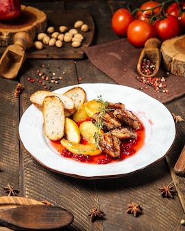 Vista lateral de frango assado com torradas de batata e molho de mirtilo