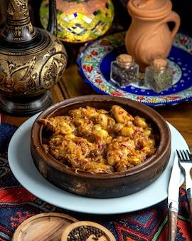 Vista lateral de frango estufado com castanhas e cebola em uma tigela de barro em uma mesa de madeira