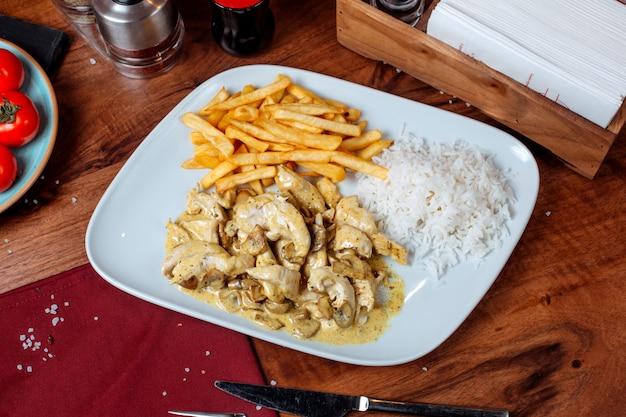 Vista lateral de frango estufado em molho cremoso com cogumelos, guarnecidos com batatas fritas em um prato branco