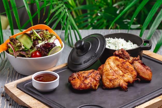 Vista lateral de frango frito com arroz cozido em uma panela e salada de legumes com molho