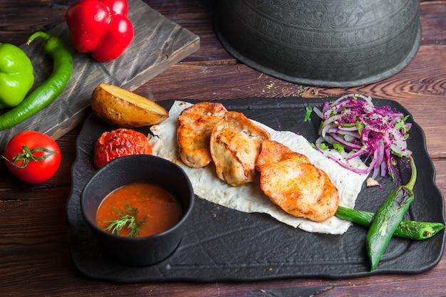 Vista lateral de frango grelhado com batatas, tomate, cebola, pimenta e molho em uma mesa de madeira escura horizontal