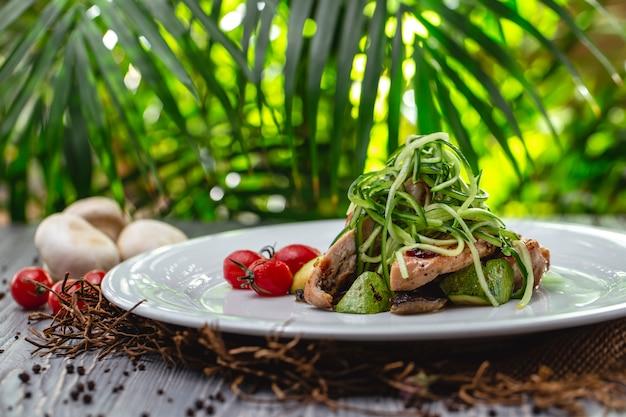 Vista lateral de frango grelhado com cogumelos abobrinha de tomate e pepino em um prato
