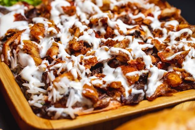 Vista lateral de frango grelhado com maionese e guarnição de arroz em uma bandeja