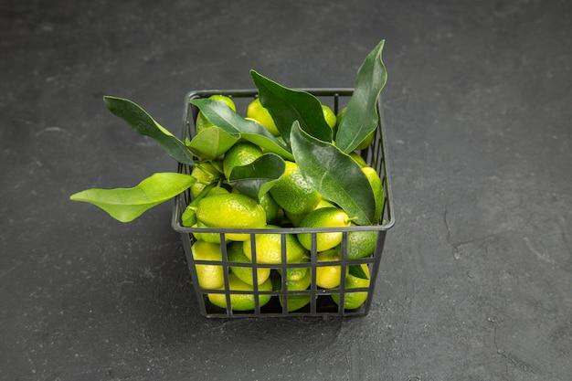 Vista lateral de frutas a cesta de frutas com folhas na mesa escura