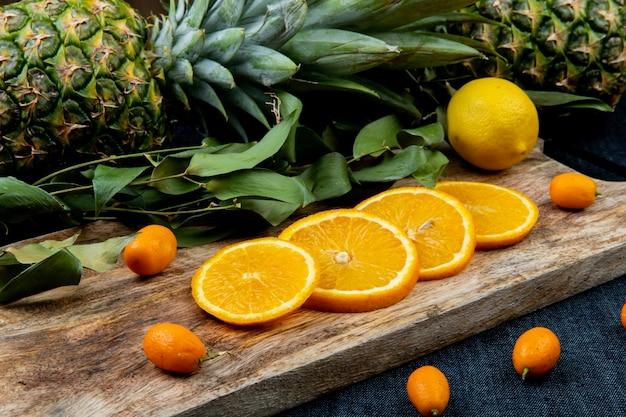 Vista lateral de frutas cítricas como laranja e kumquat com folhas na tábua com abacaxis no fundo de pano de calça jeans