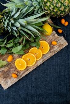 Vista lateral de frutas cítricas como limão kumquat laranja na tábua com abacaxis e folhas no fundo de pano de calça jeans