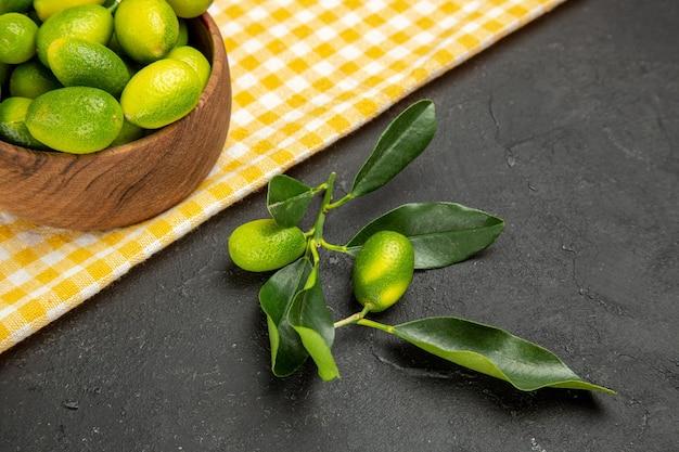 Vista lateral de frutas cítricas em close-up na tigela sobre a toalha de mesa branco-amarela