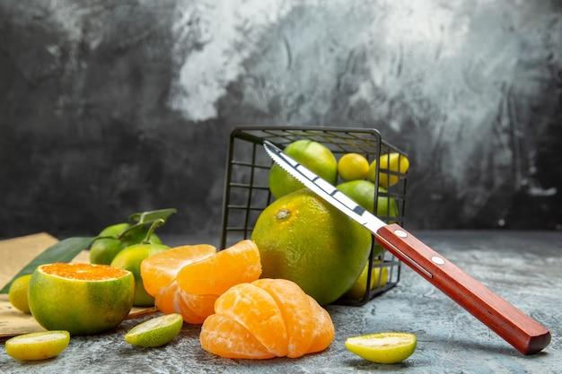 Vista lateral de frutas cítricas frescas com folhas caídas de uma cesta preta cortada ao meio e uma faca no jornal sobre fundo cinza