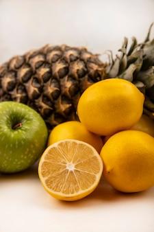 Vista lateral de frutas, como abacaxi, maçã verde e limões, isoladas em uma parede branca