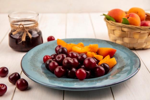 Vista lateral de frutas como cerejas e fatias de damasco no prato e cesta de damascos com geléia de morango no fundo de madeira