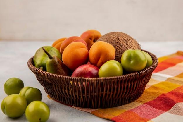 Vista lateral de frutas como coco, damasco, pêssego, pêra, em uma cesta em pano xadrez com ameixas no fundo branco