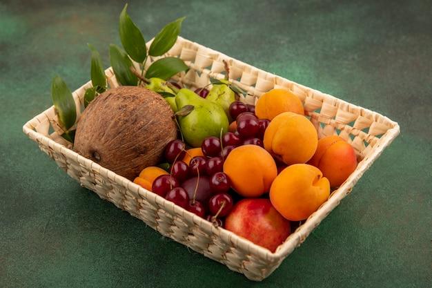 Vista lateral de frutas como coco, pêssego, damasco, pera cereja, com folhas na cesta sobre fundo verde