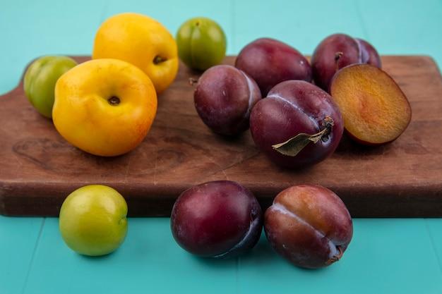 Vista lateral de frutas como nectacotes, ameixas e pluotas na tábua e no fundo azul