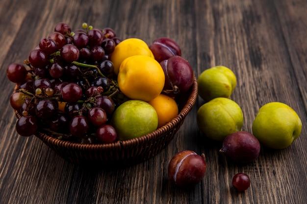 Vista lateral de frutas como nectacotes pluotas de uva na cesta e em background de madeira