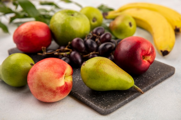 Vista lateral de frutas como pêra, maçã, uva, pêssego, numa tábua, com banana e folhas no fundo branco