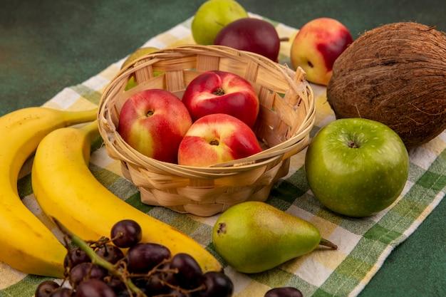 Vista lateral de frutas como pêssego na cesta e uva pêra banana coco em pano xadrez sobre fundo verde