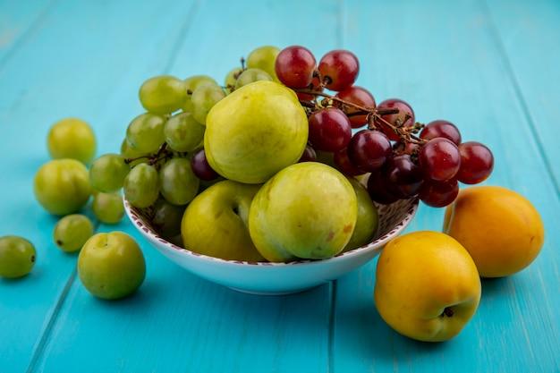 Vista lateral de frutas como plumas verdes de uvas em uma tigela e padrão de ameixas e nectaculos em fundo azul