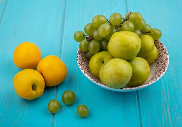 Vista lateral de frutas como uva e pluots verdes em uma tigela com nectacots e bagas de uva no fundo azul