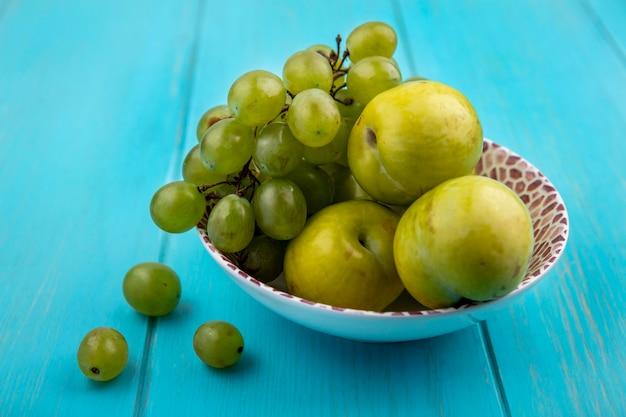 Vista lateral de frutas como uva e pluots verdes em uma tigela e bagas de uva no fundo azul