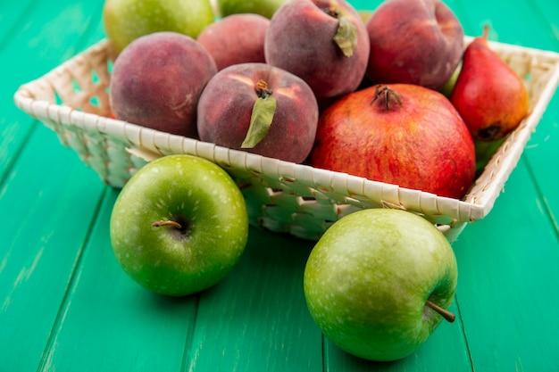 Vista lateral de frutas diferentes, como romã pêssego em um balde com maçãs verdes na superfície verde