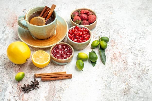 Vista lateral de frutas e chá uma xícara de chá preto de frutas cítricas, biscoitos de chocolate e canela