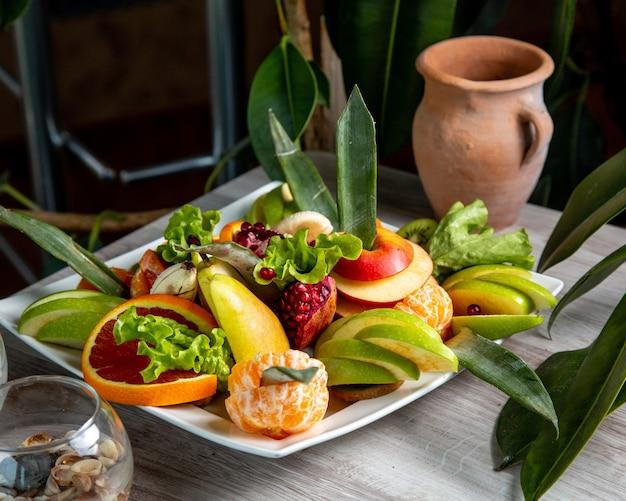 Vista lateral de frutas fatiadas em um prato toranja maçã mandarina romã
