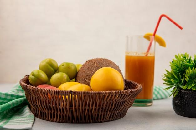 Vista lateral de frutas frescas, como cereja verde, ameixa, coco, pêssegos amarelos em um balde com suco de pêssego fresco em um copo em um fundo branco