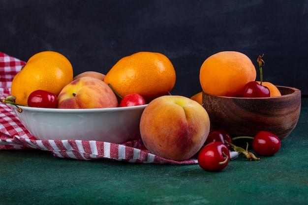 Vista lateral de frutas frescas maduras tangerinas pêssegos e cerejas vermelhas em uma tigela no tecido xadrez no escuro