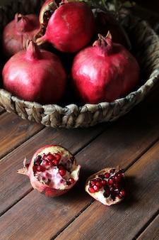 Vista lateral de frutas maduras de romã na cesta
